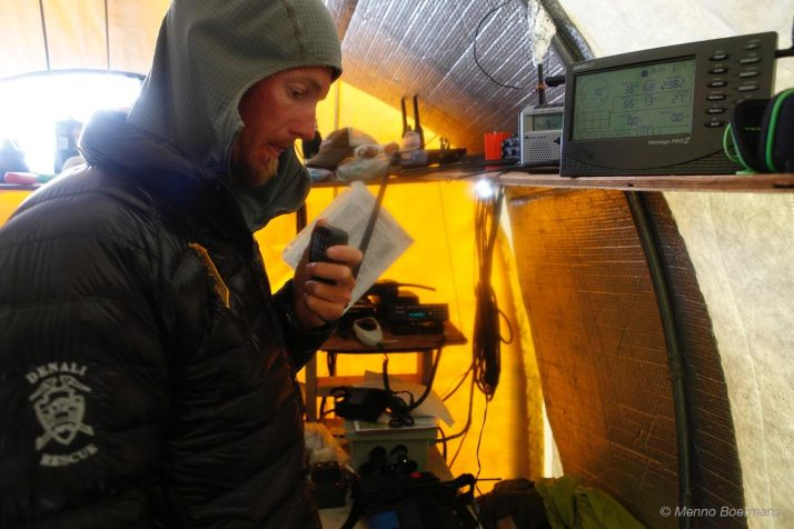 Weber monitoring radio communications during a search and rescue mission from the communications tent at 7,200 feet on Denali (photo Menno Boermans)