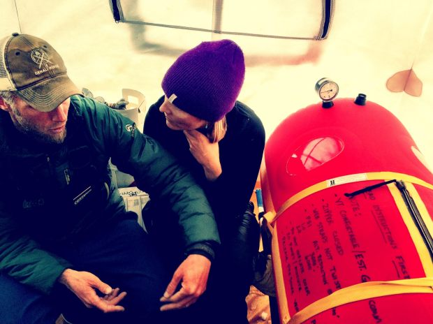 Weber and Dr Katie Russell discuss treatment strategies for a high altitude cerebral edema (HACE) patient being treated in a portable hyperbaric chamber at 14,200 feet on Denali (photo Brian Scheele)